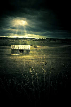 Dark Atmospheric Landscape On A Distant Outback Shed In A Farming Field, Being Lit Up By Sun Rays Piecing Clouds, Photograph Taken In Rural Tasmania, Australia photo