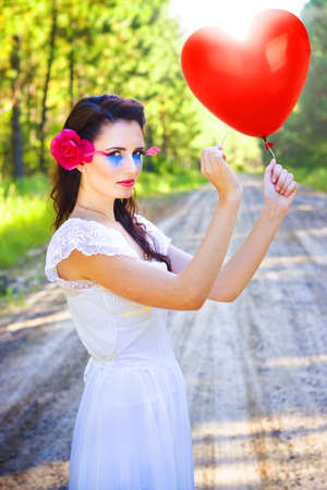 Beautiful Cupid Wearing Artist Makeup And Floral Hairpiece Holding Onto A Sharp Pin Or Needle About To Burst Or Pop A Love Heart Balloon In Heartache And Heartbreak photo