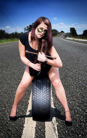 Woman Auto Tire Mechanic Stands In The Road About To Service Her Car And Change A Tyre With A Tire Wheel Brace In Hand photo