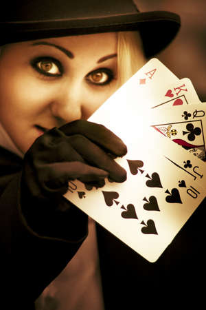 A Woman Card Magician Show Her Hand Of Playing Cards While Keeping A Poker Face In A Magic Card Trick Performance Stock Photo - 12864910