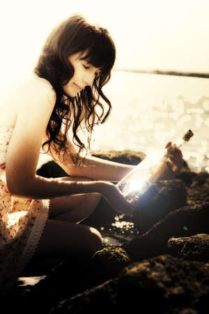 Portrait Of A Beautiful Young Woman Finding A Message In A Bottle photo