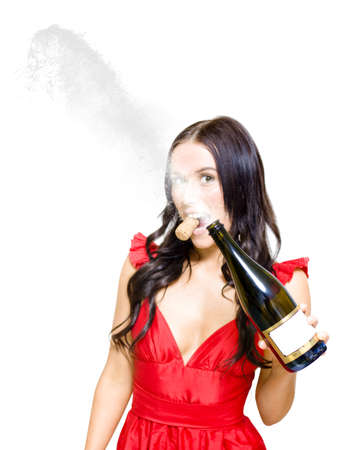 Young Attractive Woman Spraying A Uncorked Bottle Of Champagne In The Air After A Successful Business Deal, House Purchase Or Financial Win, Isolated On White photo