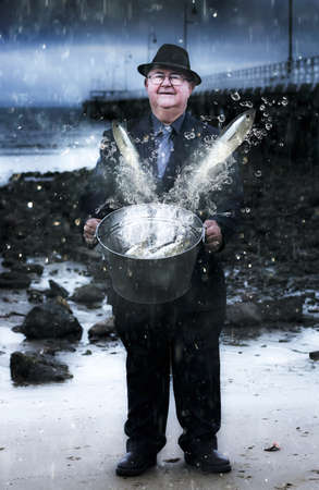 Senior Man Holding A Bucket Filled With Splashing Water And Jumping Fish Standing On A Seaside Shoreline In A Depiction Of Plentitude And Abundance photo