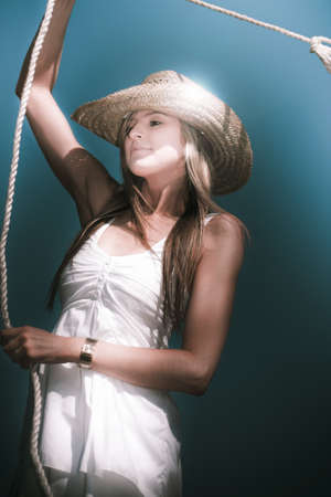 A Pretty Blond Young Woman Wearing A Straw Cowboy Hat Twirling A Lasso Against A Blue Sky Background photo