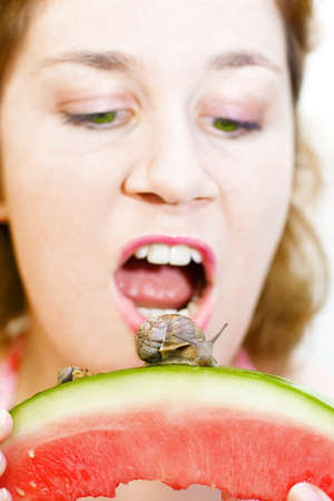 Lady Opens Her Mouth Wide To Eat The Invading Snails Sliding On The Skin Of Her Sliced Watermelon Stock Photo - 12864716