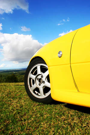 Vertical Outdoor Photograph Of A Yellow Sports Car Convertible Parked On A Green Grass Hilltop In A Driving Dreams Conceptual photo
