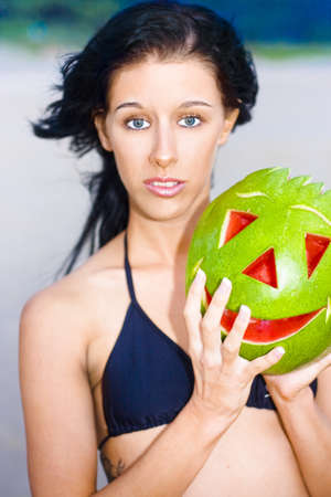 Young Woman At The Beach With Look Of Confusion While Holding A Watermelon With Carved Smiling Face Symbolizing Having Mixed Feelings That Do Not Always Match Surroundings Stock Photo - 12864221