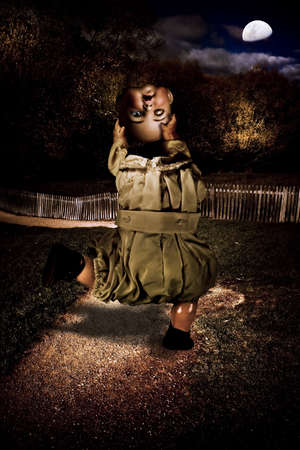 China Doll Does A Headless Dance While Watching With One Eye Open Along Pebble Path At Night In A Creepy Depiction Of Possession Haunting And Terror Stock Photo - 11591363