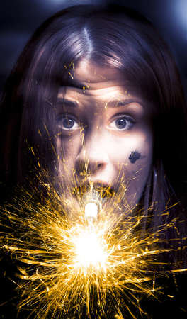 Shocked And Surprised Woman With A Spark Plug In Her Mouth Is Amazed In Shock And Surprise When A Fireworks Display Of Sparks Illuminates Her Face Stock Photo - 12864717