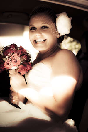 Smiling Happy Bride Holding Pink Rose Bouquet Sitting In The Car On the Way To Her Wedding With Expression Of Joy And Excitement Stock Photo - 12864730