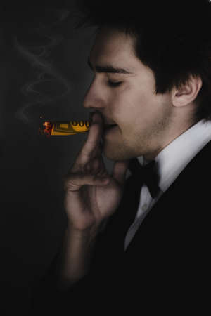 Business Man Standing In The Darkness Smoking And Burning A Hole In A 500 Dollar Bill In A Sign Of Unsustainable Excess Consumption Disorder Defined As A Societal Addiction photo