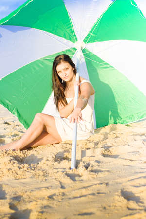 Attractive Brunette Woman Sitting On Beach With Umbrella Or Parasol photo
