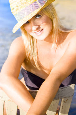 Beautiful Young Woman With Blonde Hair Wearing Sunhat Smiling Delicately With Expression Of Happiness Against Ocean Background photo