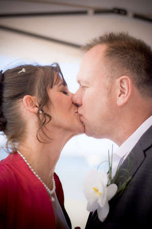 Just Married Bride And Groom Embrace In A Wedding Kiss Just After A Beach Marriage Ceremony photo