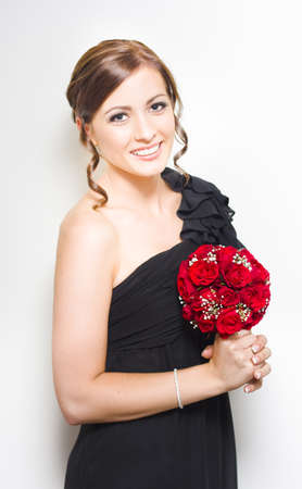 Portrait Of A Beautiful And Happy Bridesmaid With Beautiful Up-Do In Black One-Shoulder Dress Holding Red Rose Bouquet Against White Background photo