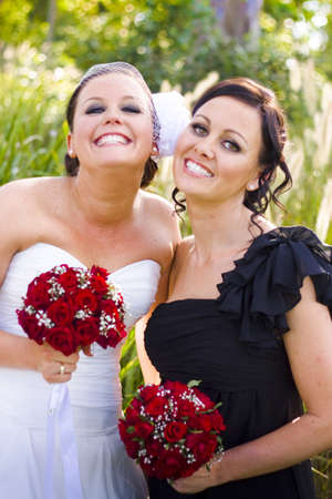 A Bride Wearing A Wedding Dress Smiling With Glee And Posing With Her Happy Maid-Of-Honor Wearing Black Dress And Showing Their Friendship And Care For One Another Against Grassy Outdoor Background photo