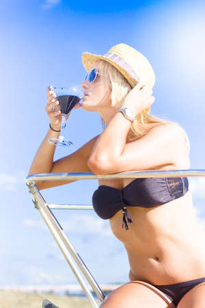 Rich Portrait Of Affluence And Wealth Sees A Blonde Lady Wearing Summertime Hat Drinking A Pina Colada Cocktail Beverage On A Boat In A Sip Of Ocean Paradise Stock Photo - 12864840