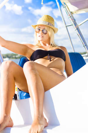 Blonde Female Boat Skipper Sitting Unwinding Resting And Tanning In The Summer Sun While On A Boating Holiday In A Scene Of Beauty And Holidays photo