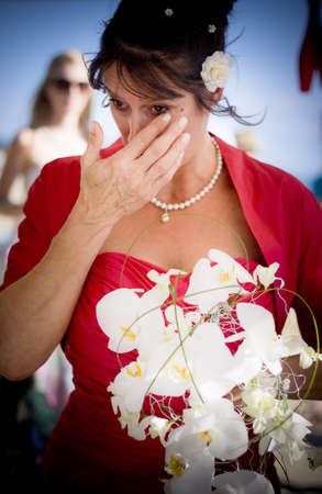 Emotional Bride Holding A Floral Bridal Bouquet Wipes A Tear From Her Eye During The Emotion From The Biggest Day Of Her Life – Her Wedding Day Stock Photo - 12864431
