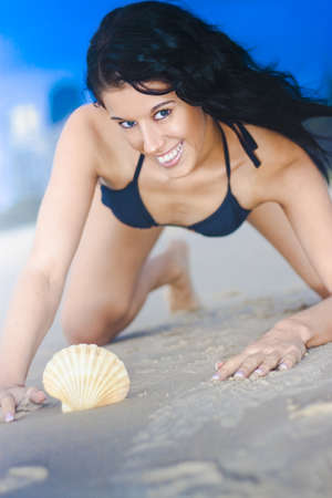 Attractive Young Bikini Female Smiling With Expression Of Happiness And Playfulness With White Seashell In Foreground And Blue Sky Background Stock Photo - 12865178