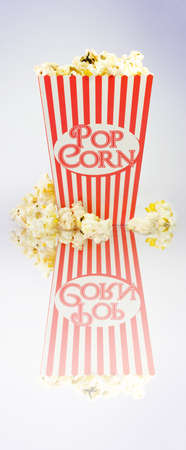 A full to overflowing iconic red and white striped popcorn carton on white with reflection photo
