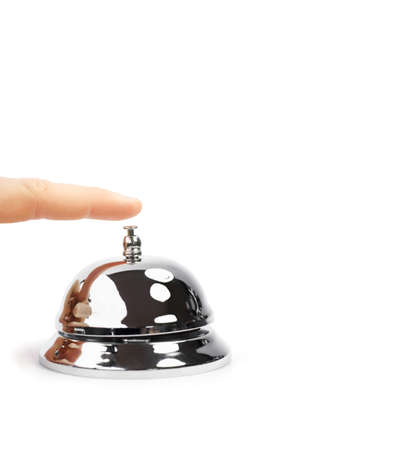 Finger Pushing Service Bell. A finger pushing a shiny domed desktop service bell in a service, hospitality and help concept. Stock Photo - 12311890