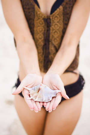 Close-Up Of A Beautiful Seashell Being Held By A Young Woman Wearing A Black Bathing Suit With Sand Colored Background photo
