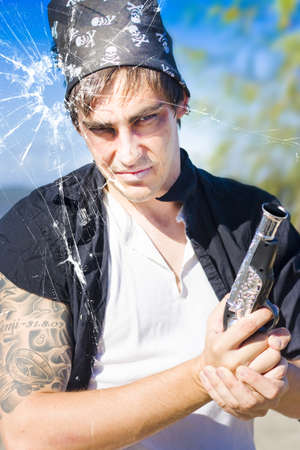 Killer Pirate Holding A Hand Gun Or Pistol Looks Through A Bullet Hole In A Fractured And Ruptured Pane Of Glass During An Assassination Killing Or Murder Stock Photo - 12864960