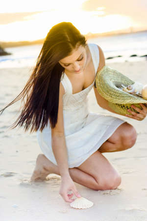 Gorgeous Brunette Woman Collecting And Gathering Sea Shells In A Hat During Sunset In A Serene Pure And Relaxing Recreation Activity photo
