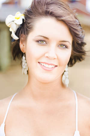 Happy Flower Girl Smiles In Delight And Happiness While Standing Outdoors With A Decorative Floral Hairpiece In Her Brunette Hair That Is Blowing In The Wind Stock Photo - 12863993