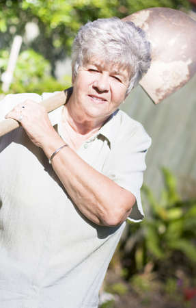Retired Gardening Grandmother Holding Garden Spade And Smiling While Doing Her Favorite Backyard Activity photo