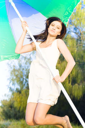 Action Excitement And Freedom Concept Sees An Active Pretty Brunette Woman Holding Parasol Jump Into The Air At A Beach Location photo
