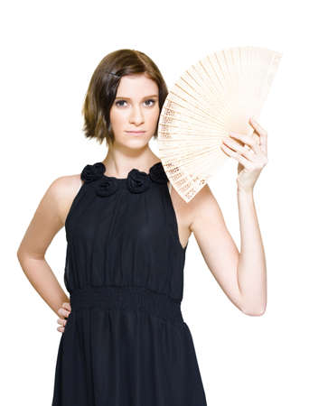 Isolated Studio Picture Of A Sexy Woman In Black Formal Evening Gown Holding An Oriental Asian Fan While Looking On Camera In A Travel Asia Concept Over White Stock Photo - 12863966