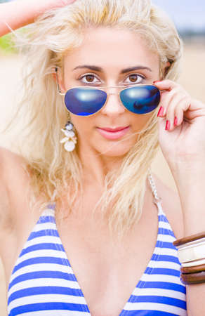 Young Beautiful Sexy Tanned Woman In Blue Sunglasses And Retro Blue Swimmers Stands Peering Over Her Glasses In A Summer Vacation Beach Concept photo
