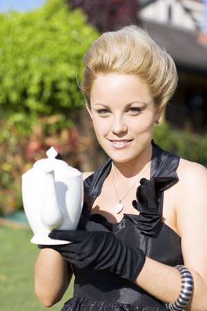 High Tea Woman Standing Outside In Her Front Garden Holding A Teapot During A High Tea Party photo