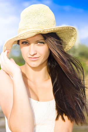 Portrait Of A Hot And Sexy Wind Swept Beach Babe Wearing Hat With Beautiful Blue Sky In The Background. photo