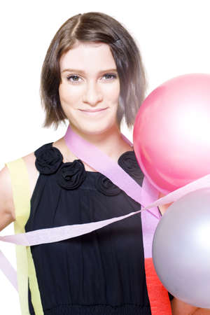 Isolated Close-up Portrait On The Happy Face in A Cute Girl Draped In Party Balloons And Streamers In A New Years Eve And Birthday Celebration Conceptual, Over White photo