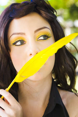 Creative Writing Concept With A Novelist Dreaming Thinking And Imagining Up The Words And Chapters To Her Story While Holding A Yellow Quill Outdoors Stock Photo - 12864454