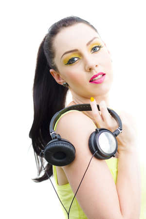 Isolated Studio Portrait Of A Sexy DJ Girl Carrying A Set Of Stereo Earphones Or Headphones On Shoulder In An Audio Electronics Technology And Sound Concept photo