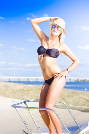 Female Tropical Beach Traveling Tourist On Sightseeing Tour While On Ocean Vacation Standing On A Speed Boat Or Ocean Cruiser, Holiday Travelling Concept photo