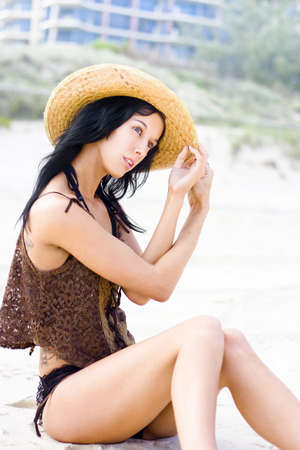 Attractive Female With Black Hair Sitting On The Beach With Expression Of Discovering A New And Beautiful Place As If She Wanders From Beach To Beach photo