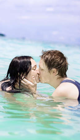 Young Man And Woman Couple Kissing In The Sea Of Romance While On Their Honeymoon Vacation photo