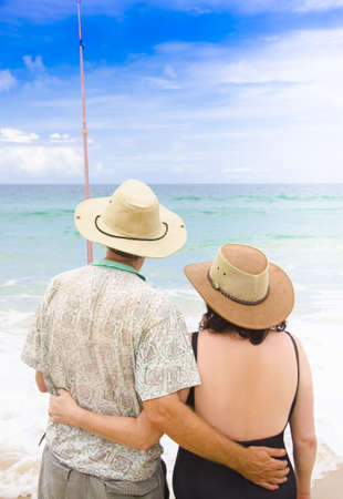 Senior Couple Stand In Each Others Arms While On A Recreation Fishing Holiday At A Tropical Beach Location, Photograph Taken Bribie Island In Queensland Australia photo