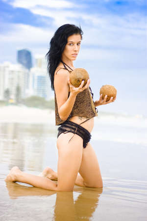 Beautiful Shoreline Female Kneeling In Shallow Water Holding Two Coconuts With A Ethereal Expression Of Prettiness With A Beach City Background photo
