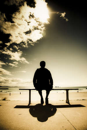 Creative Outdoor Photo Of A Young Man In Silhouette Sitting In The Sun On A Park Bench At A Australian Beach, Photograph Taken Wategos Beach, Byron Bay Australia photo