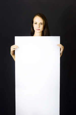 Isolated Photo Of A Gorgeous Brunette Business Woman Smiling While Showcasing Product Savings And Advertising Copyspace On A White Blank Board, Black Background photo