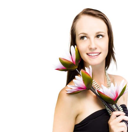 Elegant sophisticated woman in a black strapless dress and glittering necklace holding three exotic flowers over her shoulder looks back up into the frame photo