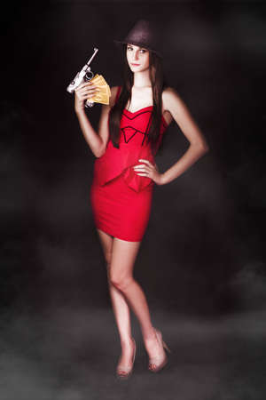 Seductive woman gangster standing in sexy red dress with extorted money and a gun in a portrayal of a vamp photo