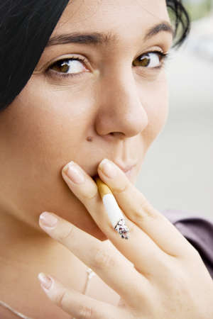 Young Woman Inhaling Smoke From A Lit Cigarette With A Mischievous Look Of Guilt photo