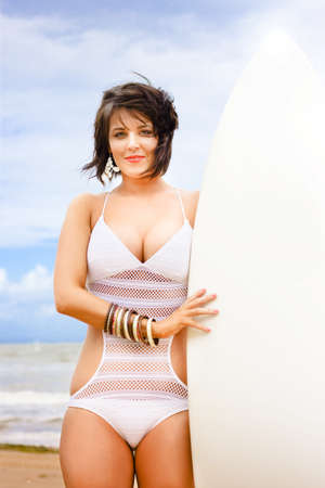 Fit Young Attractive Healthy Woman Stands Holding Surfboard On A Beach In A Health And Fitness Water Sports Conceptual photo